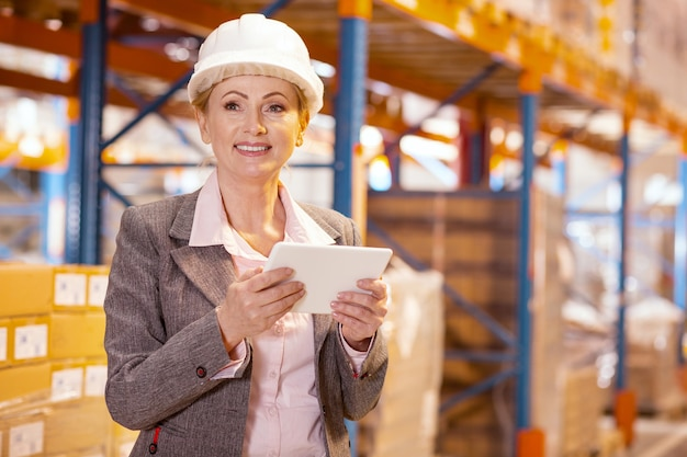 Joyful smart businesswoman holding a tablet while being in her storehouse