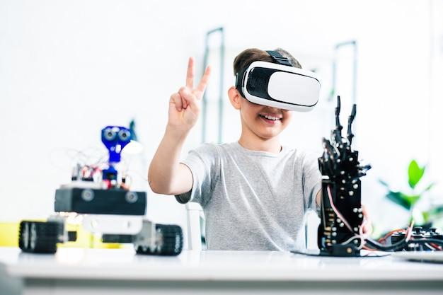 Joyful smart little boy preparing his engineering project while testing humanoid robotic hand