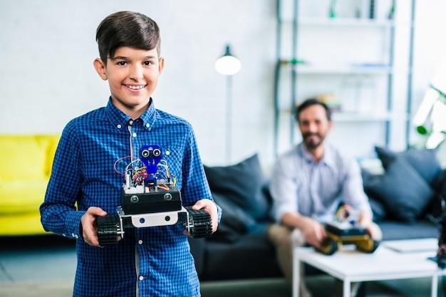 彼の父がバックグラウンドで座っている間、彼のロボットがエンジニアリングコンテストの準備をしているのを見せているうれしそうな賢い男子生徒