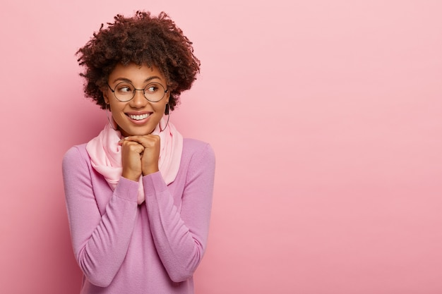 즐거운 미소 사랑스러운 여성은 턱 아래에 양손을 유지하고, 옆으로 보이는, 캐주얼 옷을 입고, 핑크 스튜디오 배경 위에 절연 안경을 착용