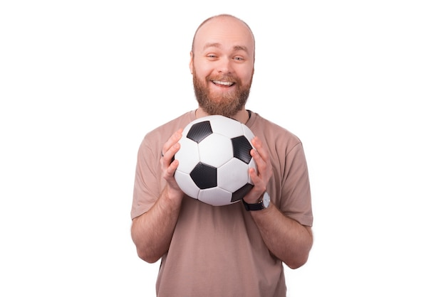 Радостный улыбающийся бородатый битник мужчина держит футбольный мяч и смотрит в камеру