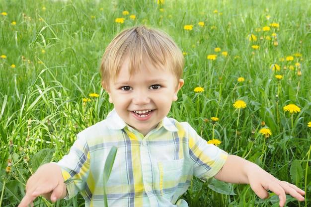 Радостный улыбающийся мальчик двухлетнего блондина с карими глазами в рубашке на поляне с зеленой травой и жёлтыми одуванчиками.