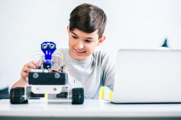 Радостный улыбающийся мальчик пробует робота во время подготовки к инженерным занятиям дома