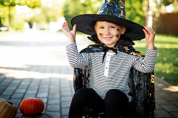 모자와 비옷의 마법사로 옷을 입고 즐거운 웃는 아이가 거리에 찌르는 데 앉아있다.