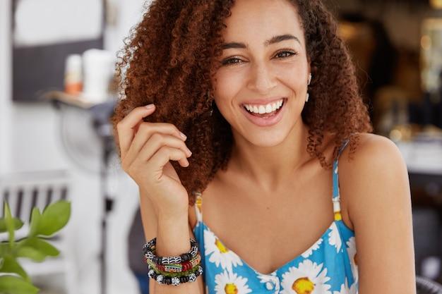 Радостная улыбающаяся темнокожая женщина с густой прической носит летнюю футболку и браслет
