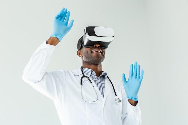 Радостный улыбающийся врач тестирует очки vr, стоя у белой стены