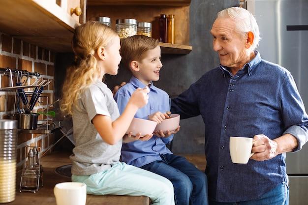 Радостный улыбающийся пожилой мужчина пьет чай, наслаждаясь временем со своими внуками