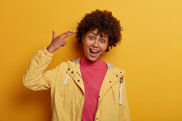 즐거운 미소 짓는 웃기는 여자가 자살하는 것처럼 손가락을 사원에 가리키고, 뇌를 날려 버리고, 머리를 기울이고, 어리 석고, 장난스런 분위기를 가지고 있습니다.