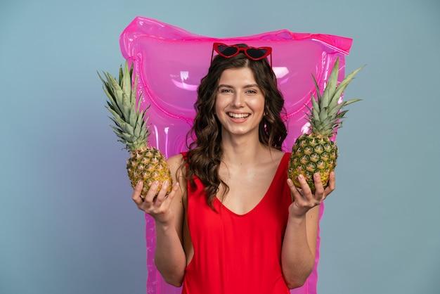 ピンクの膨脹可能なマットレスの背景にパイナップルを保持しているうれしそうな、笑顔の女の子