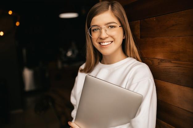 흰색 재킷에 노트북으로 즐거운 웃는 소녀. 격리 된 배경