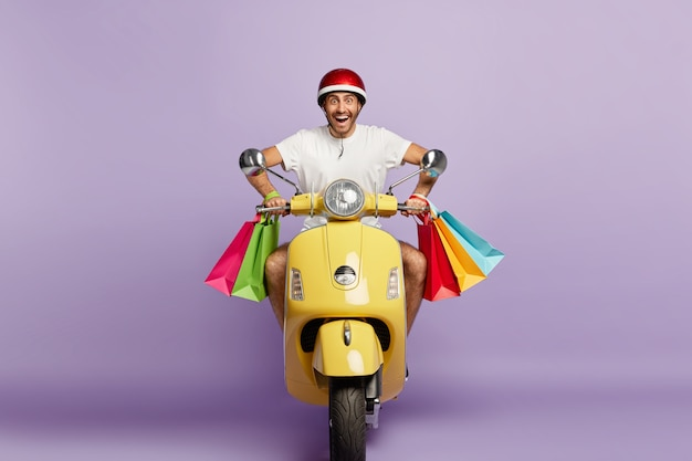Joyful smiling guy with helmet and shopping bags driving yellow scooter