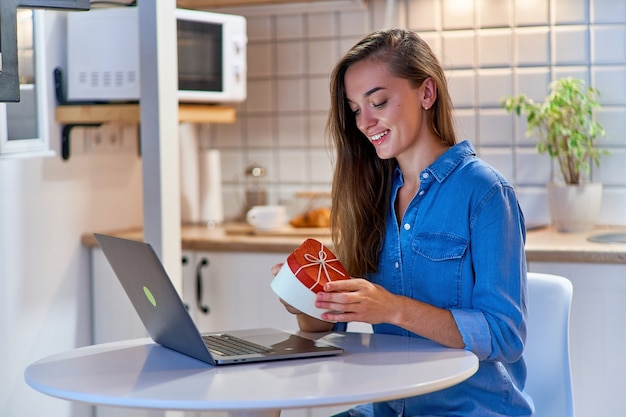 즐거운 웃는 행복한 사랑하는 여성이 온라인 발렌타인 데이 선물 상자를받습니다.