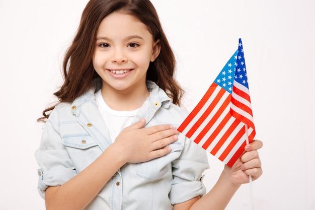 Радостная улыбающаяся маленькая девочка держит американский флаг и трогает ее грудь, выражая любовь и стоя изолированной в белой стене