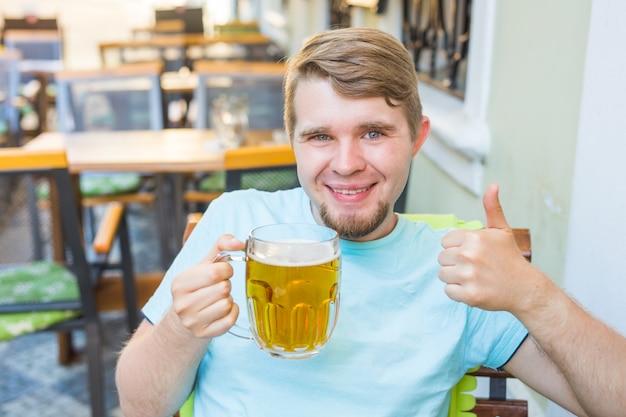 大きなビールジョッキを持って、屋外で親指を見せてうれしそうな笑顔の男