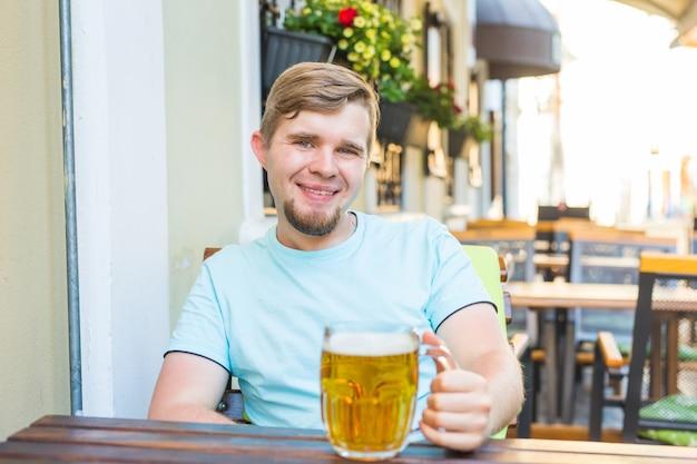 屋外で大きなビールジョッキを持ってうれしそうな笑顔の男