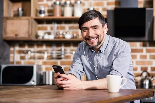 Радостный улыбающийся человек сидит за столом, используя свой смартфон и слушая музыку