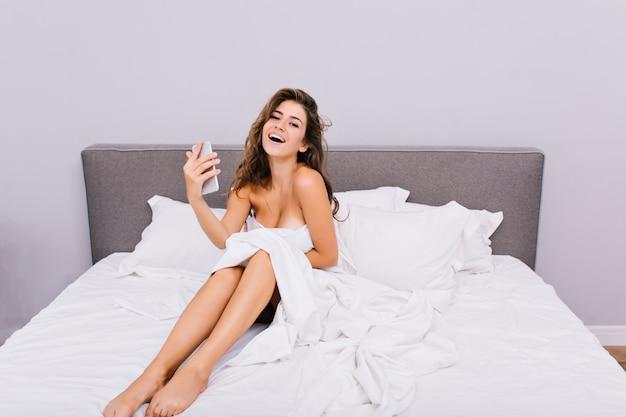 Ragazza nuda sorridente allegra con capelli lunghi che si raffreddano nel letto bianco la mattina in appartamento moderno vere emozioni positive, godersi il relax, divertirsi, bellissima modella, piacere.