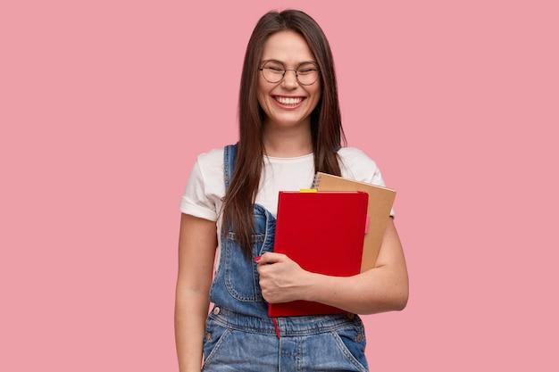 Gioiosa ragazza adolescente sorridente con un'espressione compiaciuta, porta due libri di testo, ha un sorriso a trentadue denti, ride di qualcosa di buono