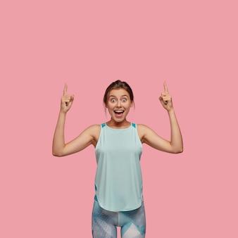 즐거운 웃는 젊은 여성은 스포티 한 몸매를 가지고 있습니다.