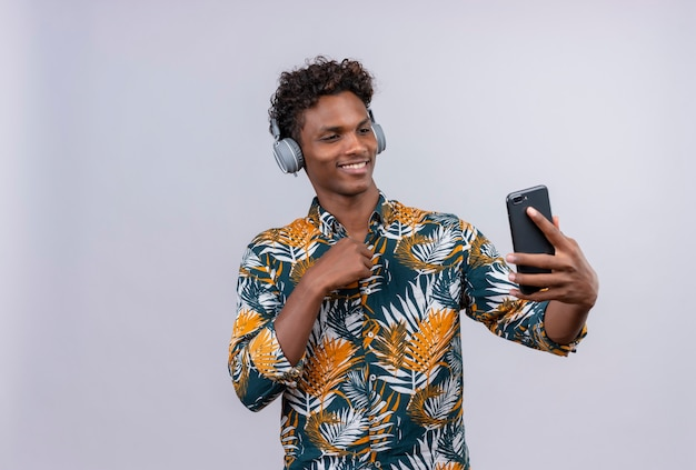 Joyful and smiling young handsome dark-skinned man with curly hair in leaves printed shirt wearing headphones looking at his mobile phone on a white background