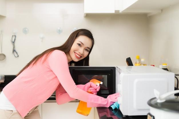 분무기로 국내 부엌에서 청소하는 앞치마를 입고 즐겁게 웃고 있는 젊은 여성