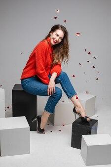 빨간 스웨터를 입고 축제 색종이 아래 즐거운 웃는 젊은 여자, 스튜디오에서 흑백 큐브에 포즈 청바지