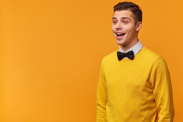 Joyful sociable excited attractive guy, smartly dressed in a yellow sweater with bow-tie, looks happy smiling