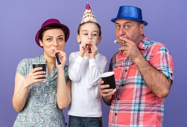 パーティーハットをかぶって、コピースペースで紫色の壁に隔離された紙コップを保持している彼の母と父とパーティーの笛を吹くうれしそうな息子