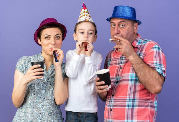 Joyful son blowing party whistle with his mother and father wearing party hats and holding paper cups isolated on purple wall with copy space