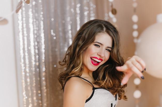Радостная эффектная темноволосая девушка лукаво смотрит и показывает пальцем. фотография женщины, позирующей на блестящей стене