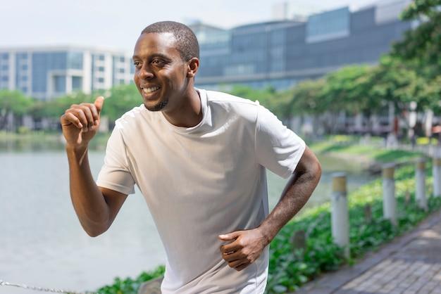Joyful sporty black guy running by city pond.