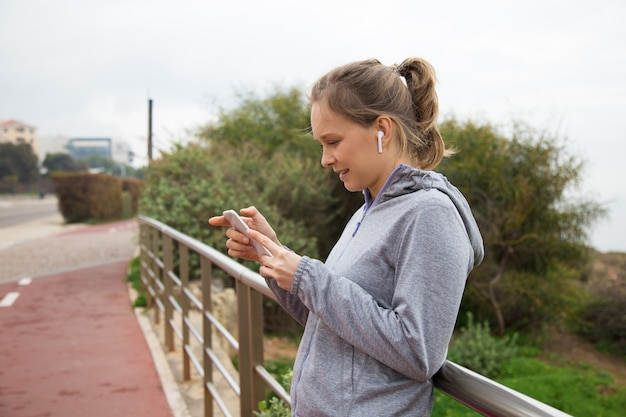 Joyful sporty girl stop jogging and checking up app