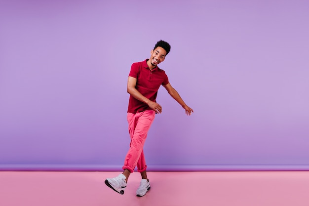 幸せを表現するピンクのパンツでうれしそうなスポーティーな男。感情的な黒人の若い男が踊っています。