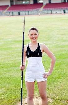 Joyful sporty woman holding a javelin standing in a stadium