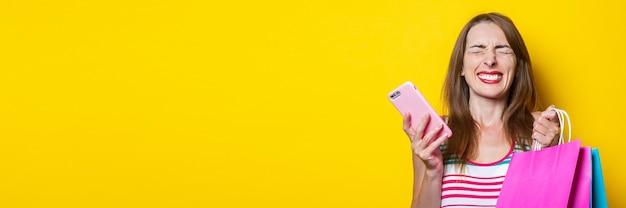 노란색 배경에 쇼핑백을 들고 전화기를 들고 즐거운 곁눈질을 하는 어린 소녀. 배너.
