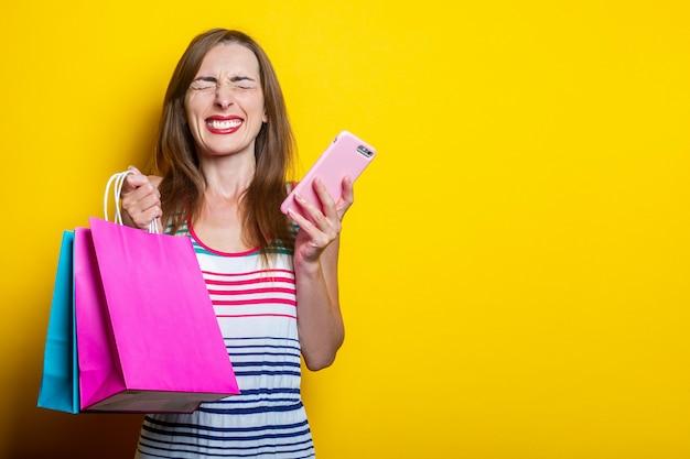 Радостная косоглазая молодая девушка с телефоном, держащая хозяйственные сумки