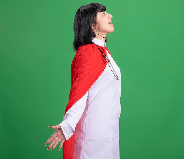 Joyful standing in profile view young superhero girl wearing stethoscope with medical robe and cloak spreading hands isolated on green wall