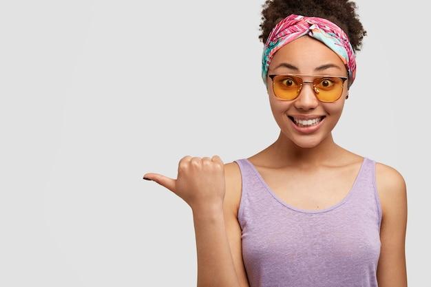 Gioiosa ed elegante signora nera indossa una fascia colorata, sfumature gialle e gilet viola, indica da parte, felice di pubblicizzare un nuovo articolo in negozio, si rallegra di sconti, isolato su muro bianco, copia spazio