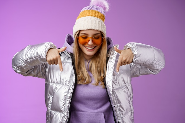 Радостная стильная белокурая женщина в серебряной куртке, стильные солнцезащитные очки jat, наслаждаясь прекрасным видом на горы, смотрит на снежный курорт, указывая вниз, улыбается, веселится, веселится, чувствует себя счастливым, фиолетовый фон.