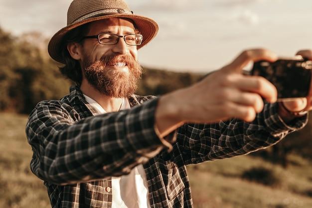 Joyful stylish male traveler taking selfie with smartphon