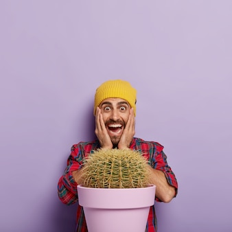 Joyful stylish man keeps hands on cheeks, looks gladfully, receives big cactus in pot as present, wears yellow hat