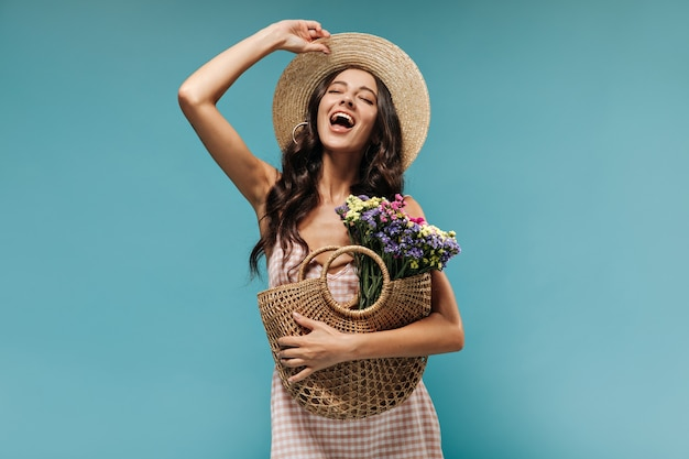 Joyful stylish woman with long curly hair in modern hat and plaid clothes screams and posing with straw bag and colorful flowers