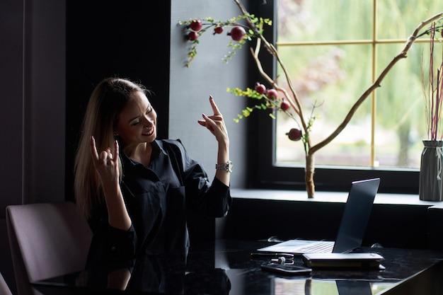 うれしそうな成功した魅力的な若い自信を持って女性はノートパソコンと職場に座って、勝利を祝う日記とスタイリッシュな黒のシャツを着ています。