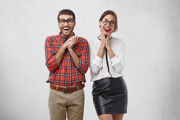 Радостные успешные деловые люди в строгой одежде радуются увеличению продаж, восхитительно выглядят