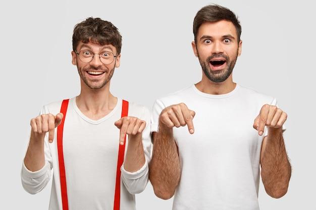 うれしそうな成功した男の同僚や友人は、白い服を着て、人差し指で下向きに、幸せな表情をしています