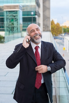 Joyful successful mature businessman talking on cellphone