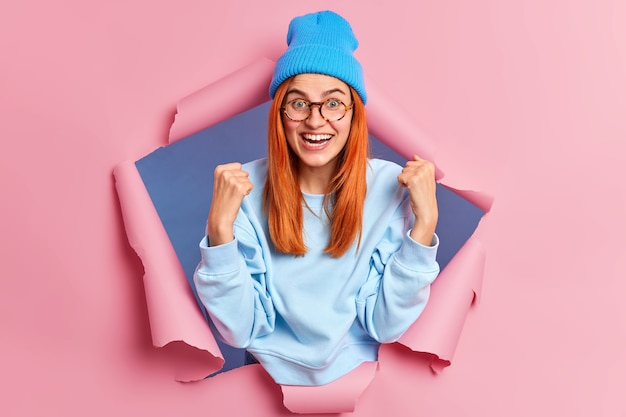 Joyful successful redhead woman happy to get victory clenches fists and smiles broadly wears blue hat sweatshirt supports favorite team breaks through paper hole
