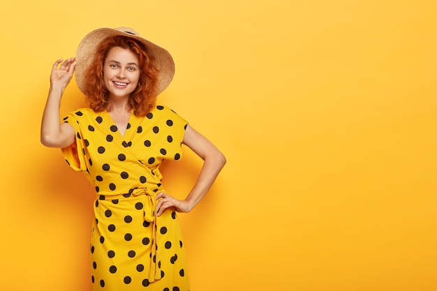 Joyful summer lady holds one hand on waist, other on straw hat, wears vivid yellow polka dot dress, has happy look, slim figure, models indoor, copy space right for your promotion. beauty and feminity
