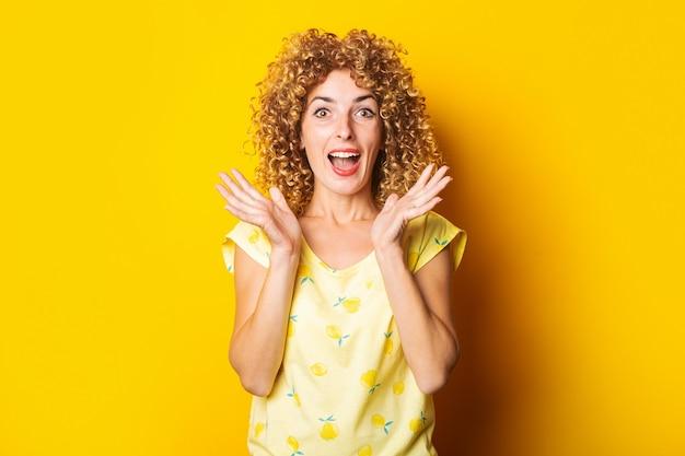 明るい黄色の背景にうれしそうな驚きのショックを受けた縮れ毛の若い女性