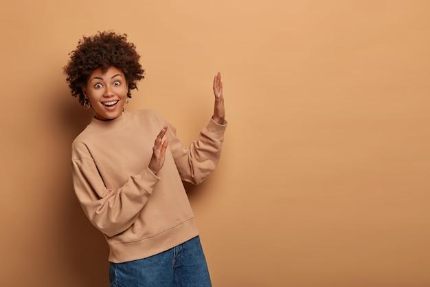 うれしそうな驚きの女性は、何かから離れて、茶色の空間に向かって手のひらを上げます